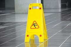 Slippery floor surface warning sign and symbol in building, hall. Office, hotel , restaurant, restroom. Concept photo danger Stock Photos