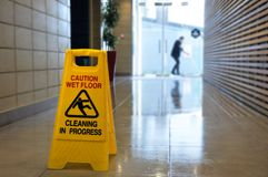 Slippery floor surface warning sign and symbol on a wet floor. Of unrecognizable building hallway Royalty Free Stock Images