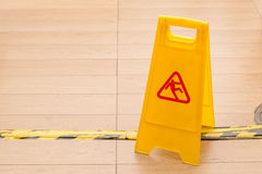 Slippery icon on yellow plastic warning sign alerts for hazard o. N floor, under construction concept stock photos