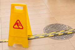 Slippery icon on yellow plastic warning sign alerts for hazard o. N floor, under construction concept royalty free stock photos