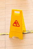 Slippery icon on yellow plastic warning sign alerts for hazard o. N floor, under construction concept stock image