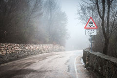 Slippery road in rainy weather, warning roadsign. Stands on mountain roadside, rural landscape stock photos