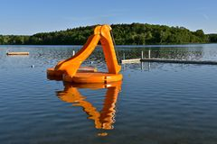 Slippery slide for outdoor recreation and swimming in a lake. Swimming area in a lake with a dock. raft and slippery slide for children Royalty Free Stock Photography