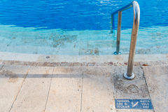 Slippery steps down to swimming pool with blue water and watch your step sign in both English and Spanish Royalty Free Stock Images