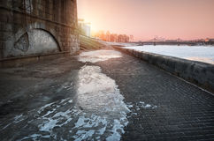 Slippery on the waterfront. Starovolzhsky bridge under sunset pink sky and the ice-covered embankment Royalty Free Stock Photography