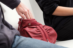 Slipping into a bag. A thief slipping his hand into a woman's red leather bag Royalty Free Stock Image