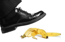 Slipping on banana peel. Businessman stepping on banana peel, close to fall down, isolated on white background Royalty Free Stock Photo