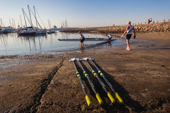 Rowing Oars Canoe Regatta. Athlete crew canoe team  going off slipway entry into the water in the early morning light Royalty Free Stock Photo