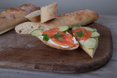 Slised Freshly Baked Baguette with Smoked Salmon on Wooden Board Royalty Free Stock Photos