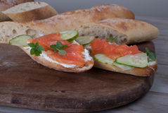 Slised Freshly Baked Baguette with Smoked Salmon on Wooden Board Royalty Free Stock Photo