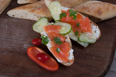 Slised Freshly Baked Baguette with Smoked Salmon on Wooden Board Stock Photos