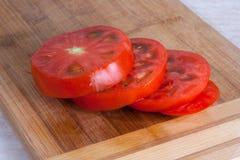 Slises der frischen Tomate auf einem hölzernen Schneidebrett Lizenzfreie Stockfotografie