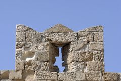 Slit on castle wall. Part of castle with crenellation. Rhodes Town in Greece Royalty Free Stock Images