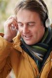 Slitage hörlurar för man och lyssna till musik Royaltyfri Bild