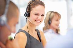 Slitage hörlurar med mikrofon för ung affärskvinna arkivbilder