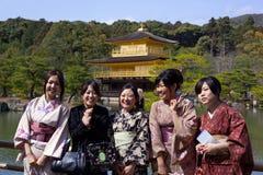 Slitage kimono för ung kvinna, guld- paviljongtempel Fotografering för Bildbyråer