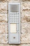 Sliten ringklocka med högtalaranläggningen på en husvägg Fotografering för Bildbyråer