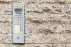 Sliten ringklocka med högtalaranläggningen på en husvägg Royaltyfri Fotografi