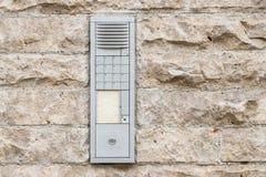 Sliten ringklocka med högtalaranläggningen på en husvägg Royaltyfri Foto