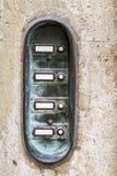 Sliten ringklocka med högtalaranläggningen på en husvägg Royaltyfria Bilder