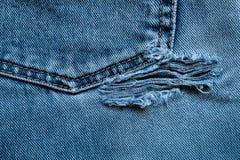 slitet rivet gammalt för jeans arkivfoto