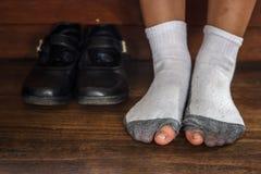 Slitet smutsa ner ut sockor med ett hål och tår som klibbar ut ur dem på gammalt trägolv. Arkivbild