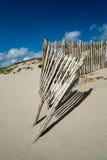 Slitet trästaket på den sandiga stranden med blå himmel Royaltyfria Foton