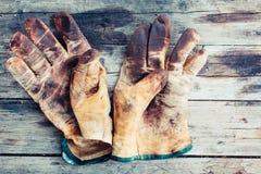Slitna läderarbetshandskar på träbakgrund som befläckas med fett och industriell olja royaltyfri fotografi