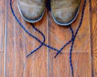 Slitna läderkängor på ett ädelträgolv Royaltyfri Bild