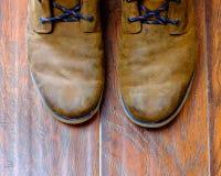 Slitna läderkängor på ett ädelträgolv Arkivfoto