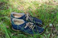 Slitna skor p? gr?s i en sommarskog royaltyfria bilder
