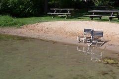 Slitna stolar på stranden för liten sjö arkivbild