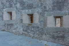 Detail of three slits of an old castle. The slits were openings in the wall of fortress to spy on and to use the  weapons against the enemies Royalty Free Stock Photo