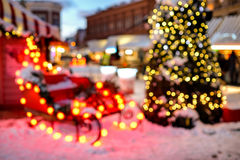 Slitta del ` s di Santa Claus ed albero di Christmass alle luci del bokeh Fondo Fotografie Stock