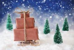 Slitta di Natale su neve con fondo, le stelle ed i fiocchi di neve blu Fotografia Stock Libera da Diritti