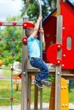 Slittamento del ragazzino giù sul palo al campo da giuoco Immagini Stock Libere da Diritti