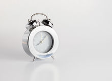 Sliver alarm clock on gery background Royalty Free Stock Image