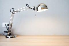 Sliver desk lamp on desk. Switch on sliver desk lamp on desk Stock Image