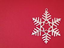 Sliver snowflake on red Stock Photography