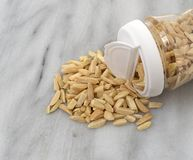 Slivered almonds spilling from container Royalty Free Stock Image