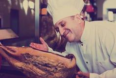 Säljaren i delikatessaffär shoppar med iberico- och serranojamon Royaltyfri Foto