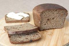 Släntra av bröd som skivas på en skärbräda Arkivfoto