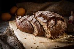 Släntra av bröd som skivas på träskärbräda Arkivfoton