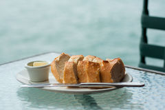 Släntra av sourdoughbröd med smör på den glass tabellen Royaltyfri Fotografi