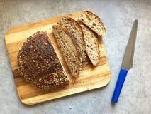 Släntrar artisanal bröd för Sourdough och skivor på träskärbräda Arkivbild