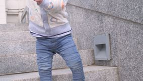 Close up of a baby boy feets in blue sneakers and jeans going down the granite ladder step by step in the city park on. Slo motion close up video of a baby boy stock video footage