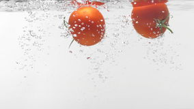 Slo-motion two tomatoes falling into water stock video footage