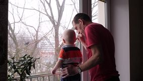 An old man and his adorable little grandson are playing by the window and grandfather show to the baby boy a bird on the