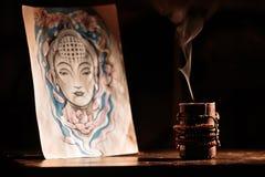 Slocknade stearinljus för härlig rök bredvid Buddha på svart bakgrund Royaltyfria Bilder