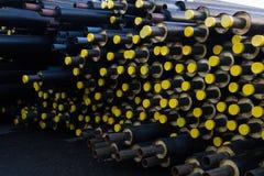 Sloeg vele zwarte staalpijp met hitteisolatie die op op bouwwerf in een plastic buisomslag met gele dekselspijpen liggen Royalty-vrije Stock Fotografie
